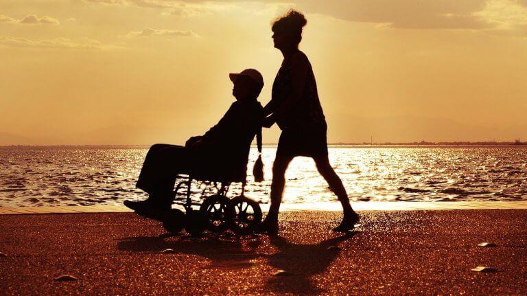 Homme dans un fauteuil roulant poussé par une femme sur la plage lors d'un soleil couchant