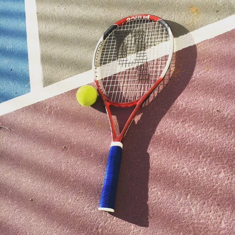 Raquette de tennis posée sur le sol avec une balle