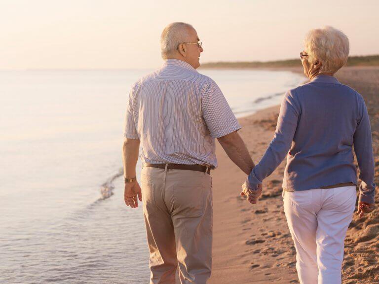 Couple de personnes âgées se promenant sur la plage