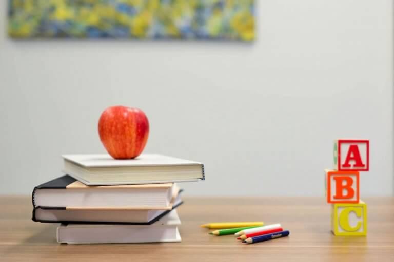 Table d'écolier avec une pile de livres, une pomme pour le goûter, des crayons de couleurs et des jouets